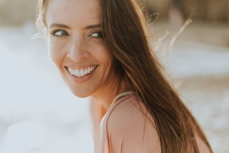 A woman at the beach smiling towards the camera wearing Invisalign clear aligners