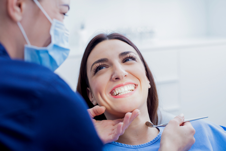 woman sitting in dentist chair getting treated by dentist.jpg